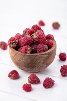 Front view of raspberries in a wooden bowl on a white surface
