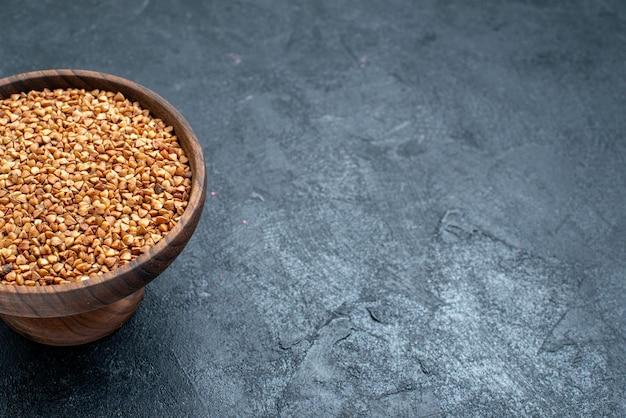 Vista frontale prodotto utile di grano saraceno crudo all'interno del piatto sulla scrivania scura