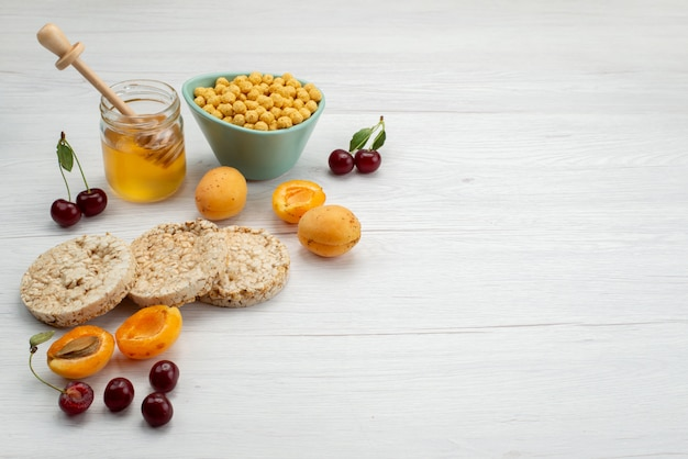 Вид спереди сырых злаков внутри тарелки с крекерами, фруктами и медом на белом, пить молоко, молочные сливки, завтрак