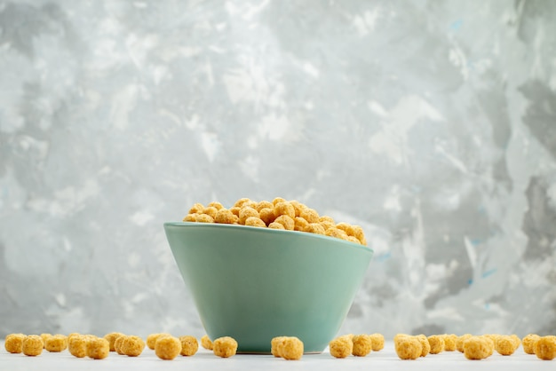 Front view raw cereals yellow colored inside green plate on white, cereal breakfast cornflakes health