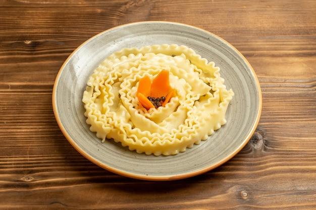 Vista frontale pasta di pasta cruda formata all'interno del piatto sulla pasta di farina di cibo crudo di pasta da tavola marrone