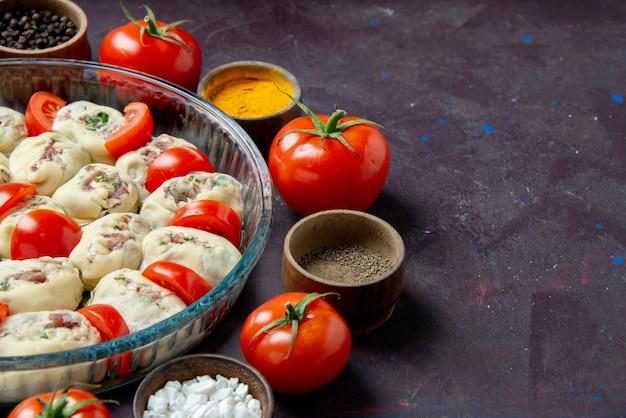 Pezzi di pasta cruda vista frontale con condimenti e pomodori su parete scura