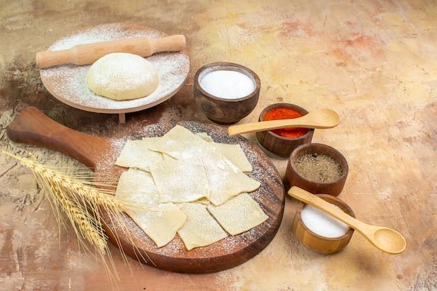 크림 책상 식사 접시 파스타에 밀가루와 조미료와 함께 전면보기 원시 반죽 조각