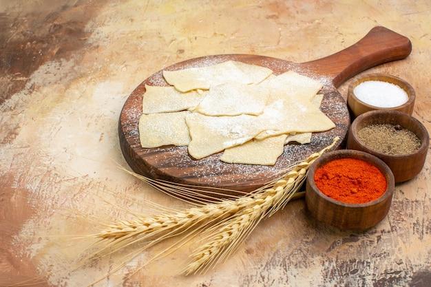 木製の机の上に小麦粉と調味料と正面の生の生地のスライス