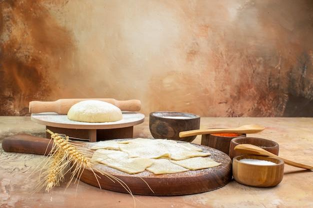 Vista frontale fette di pasta cruda con farina e condimenti sulla scrivania crema