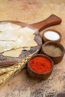 木製の机の上の調味料と生の生地スライスの正面図パスタ料理