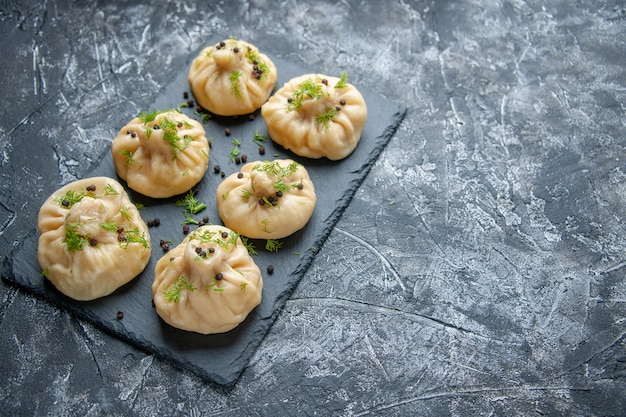 Vista frontale gnocchi crudi piccoli pezzi di pasta su sfondo grigio piatto di cucina torta cena pasto pasta cucina carne