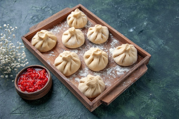 Front view raw dumplings with meat inside on dark surface cooking dish color meal flour pepper dough meat