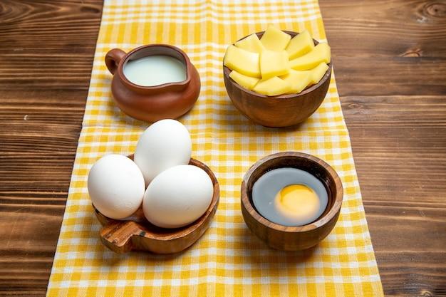 Vista frontale uova crude con formaggio e latte su una superficie in legno prodotto uova pasta pasto cibo crudo