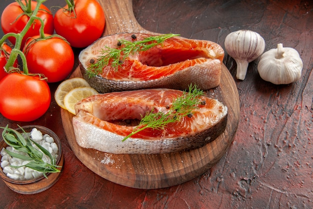 Fette di pesce crudo vista frontale con pomodori rossi su carne rosso scuro foto a colori pasto barbecue piatto di pesce