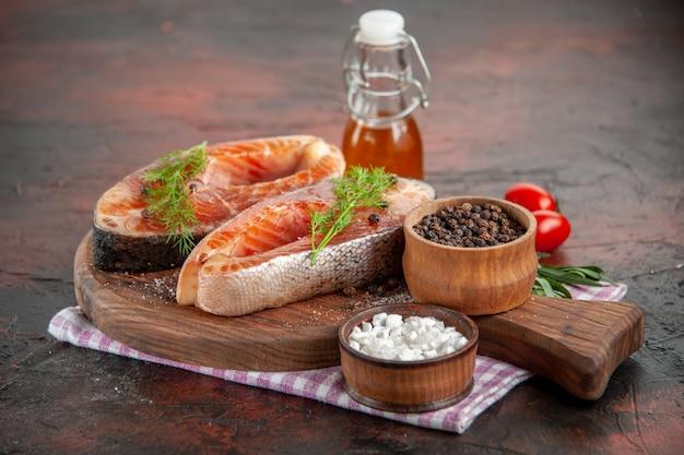 Ломтики сырой рыбы с помидорами и приправами на темном цветном мясном обеде, вид спереди