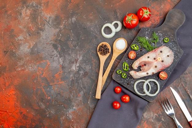 Vista frontale di pesce crudo e peperoni verdi cipolla pomodori su tagliere nero su posate asciugamano su superficie di colore misto
