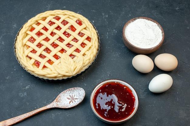 Torta di frutta cruda vista frontale con uova e farina sul tavolo scuro