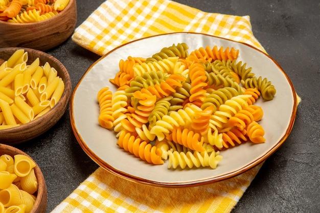 Vista frontale pasta italiana cruda diversa formata all'interno di piatti su scrivania grigia che cucina pasta italiana cruda