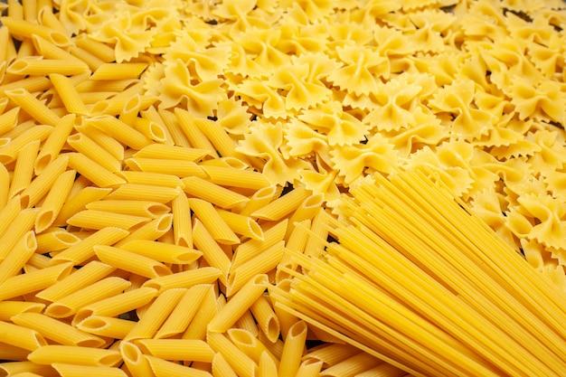 Вид спереди сырые итальянские макароны разные сформированные на светло-серой еде фото цветное тесто кухня еда