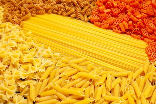 正面の生のイタリアン パスタは、明るい灰色の生地で形が異なる料理の食事写真の色の食べ物