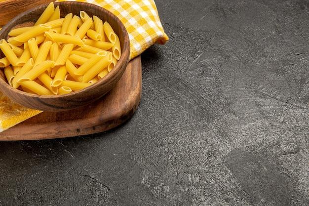 暗い灰色の空間にある茶色の皿の中の生イタリアン パスタの正面図