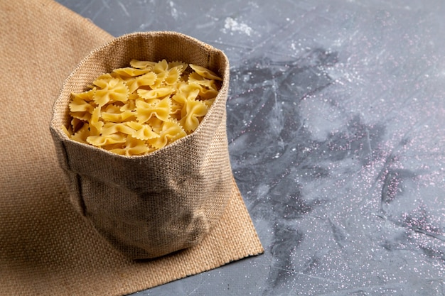 A front view raw italian pasta little formed inside bag on the grey table pasta italian food meal