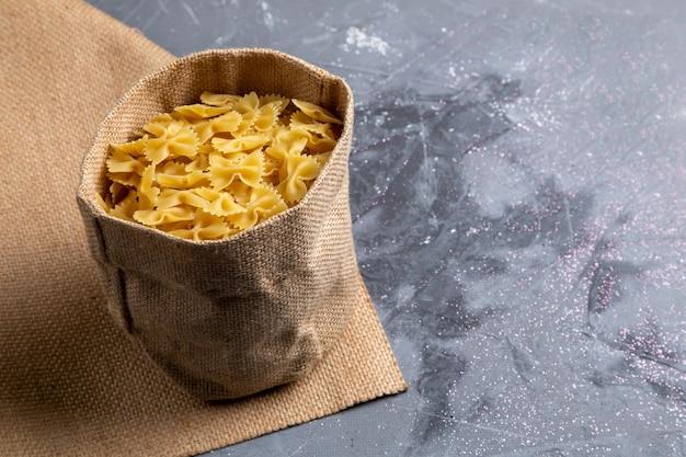 Una pasta italiana cruda di vista frontale poco formata all'interno della borsa sul pasto dell'alimento italiano della pasta da tavola grigia