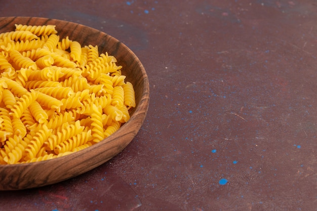 Front view raw italian pasta little formed inside plate on a dark space