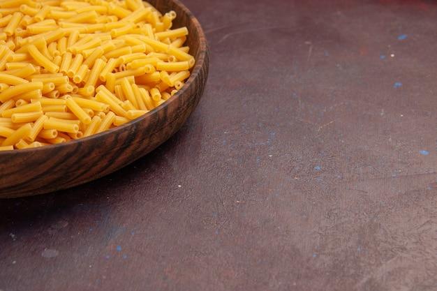 어두운 책상에 접시 내부에 약간 형성된 전면보기 원시 이탈리아 파스타