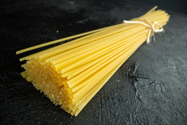 Vista frontale pasta italiana cruda lungamente formata su pasta scura colorante alimentare foto