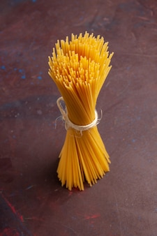 Front view raw italian pasta long formed on dark space