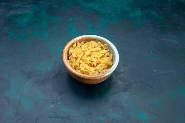 Сырые итальянские макароны на синем столе, вид спереди