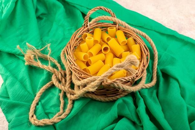 Una pasta italiana cruda di vista frontale gialla dentro il piccolo canestro con le corde sul tessuto verde