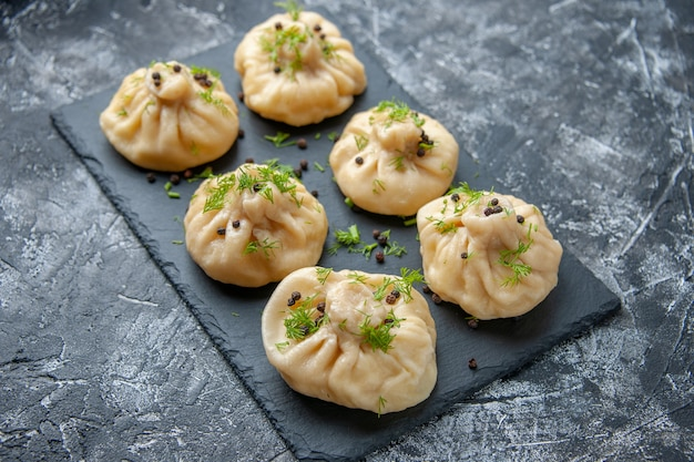 Front view raw little dumplings little dough pieces on gray surface cuisine dish dough cake dinner meal cooking meat