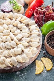 Vista frontale gnocchi crudi con farina e verdure su superficie scura