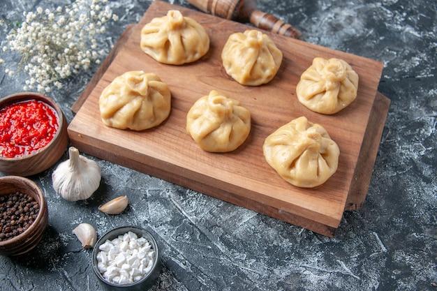 Vista frontale crudi piccoli gnocchi con carne sulla superficie grigia bordo di cottura farina colore pasta pasto piatto pepe