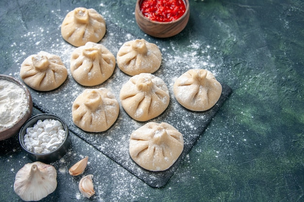 Front view raw little dumplings with meat inside on dark surface flour meat pepper color dough cooking meal cuisine dish