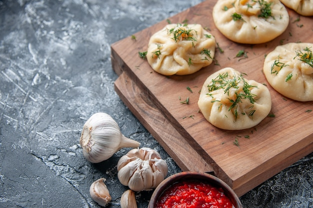 Front view raw little dumplings with meat and tomato sauce on gray surface dough pie hotcake cooking cuisine cake