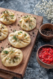 Front view raw little dumplings with tomato sauce and seasonings on a gray surface meat dough meal cake cooking dish cuisine dinner