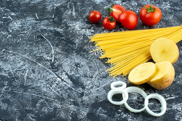 Front view raw long pasta with red tomatoes on gray background cooking color salad kitchen vegetable cuisine food