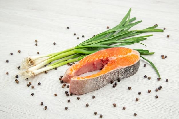 Fetta di carne cruda vista frontale con cipolla verde su sfondo bianco cibo piatto costola animale pesce