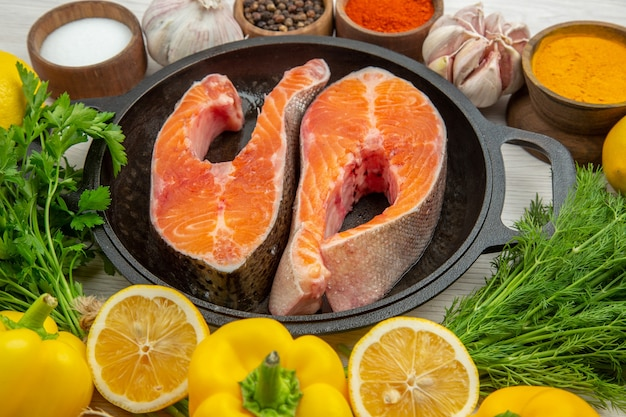 Fette di carne cruda vista frontale all'interno di una padella con condimenti verdi e verdure su uno sfondo bianco costola pasto cibo animale piatto carne