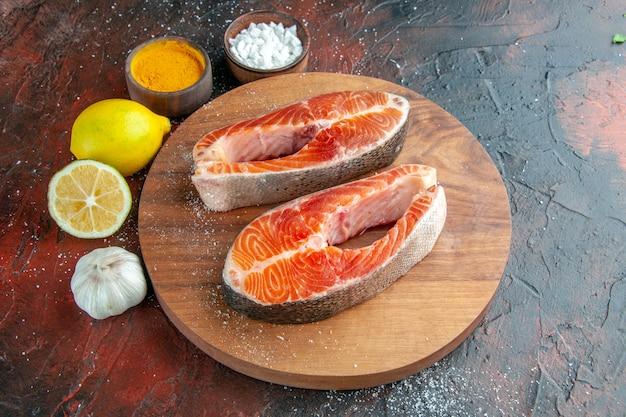어두운 배경 갈비뼈 음식 식사 동물 요리 고기에 조미료와 레몬 전면보기 생고기 조각