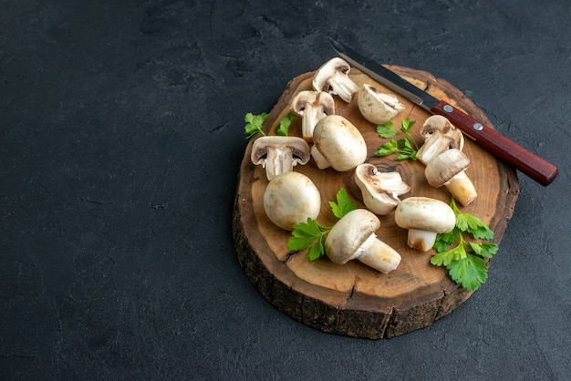 Front view of raw mushrooms and greens knife on wooden board on the left side on black background with free space