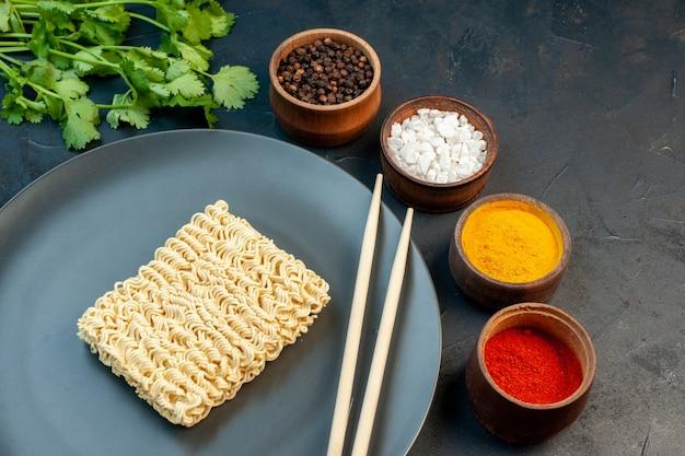 紺色のテーブルに調味料を入れたプレート内の正面図生麺