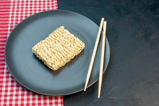 暗いテーブルに棒でプレート内の正面図生麺