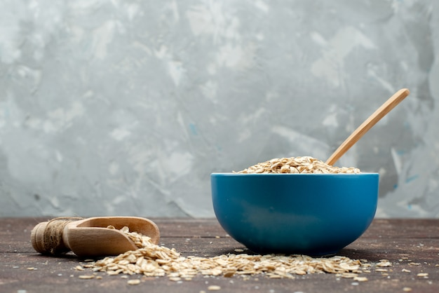 正面図ブループレート内の生のオートミールと暗い食品生健康朝食中