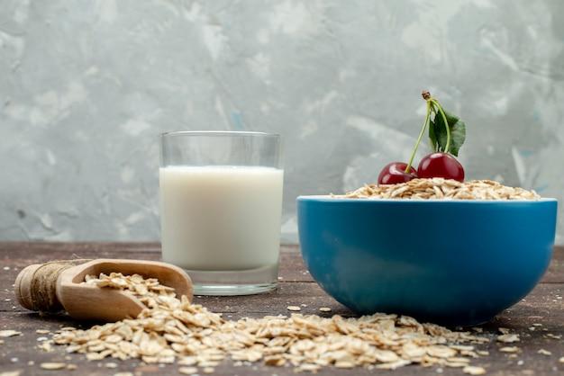 牛乳食品の生の健康的な朝食で、茶色の青いプレート内の正面生オートミール