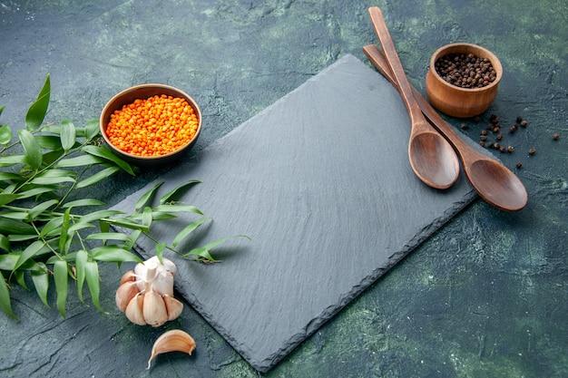 正面図生オレンジレンズ豆とニンニクと紺色の背景写真青い食べ物スパイシーな唐辛子色シャープ