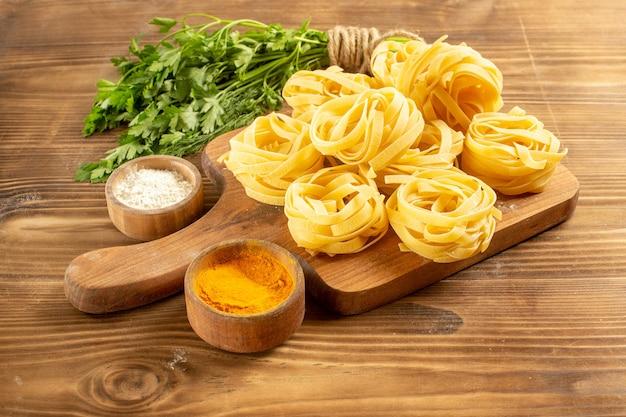 Impasto di pasta cruda vista frontale con condimenti e verdure su uno spazio marrone