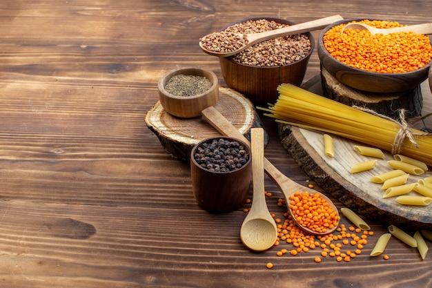 Pasta cruda vista frontale con grano saraceno e lenticchie su superficie marrone