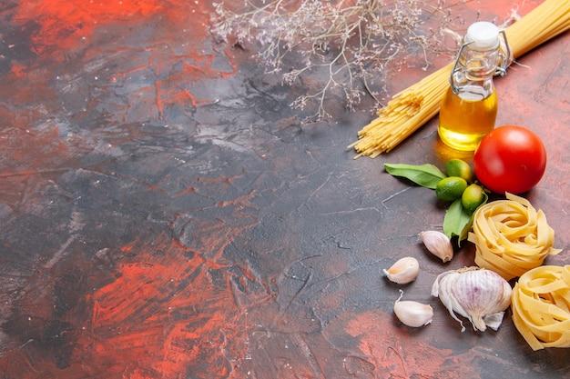 Вид спереди сырые макароны с маслом и помидорами на темной поверхности макароны из сырого теста