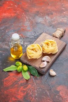 Pasta cruda vista frontale con olio e aglio sulla pasta di pasta superficie scura cruda