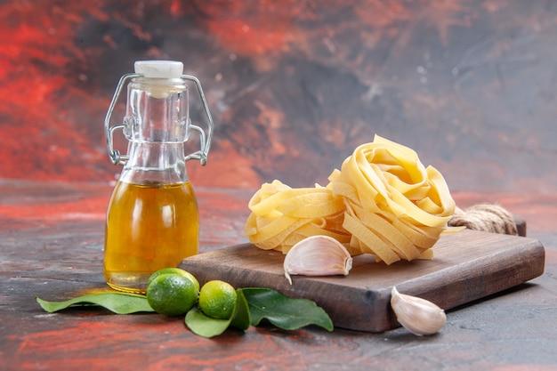 Pasta cruda vista frontale con olio e aglio su pasta di pasta superficie scura